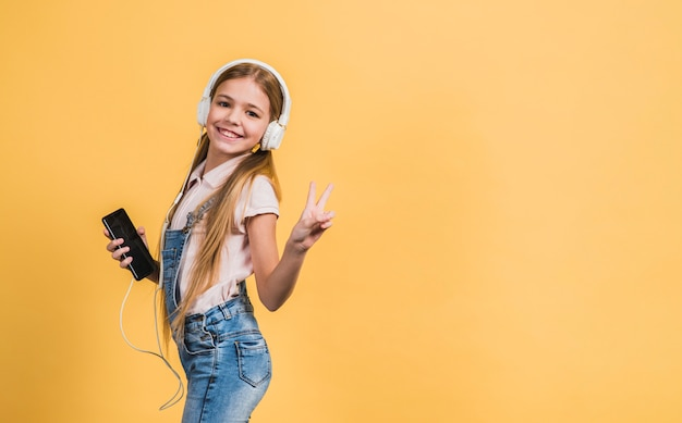 Portret uśmiechniętej dziewczyny słuchająca muzyka na białym hełmofonie gestykuluje przeciw żółtemu tłu Darmowe Zdjęcia