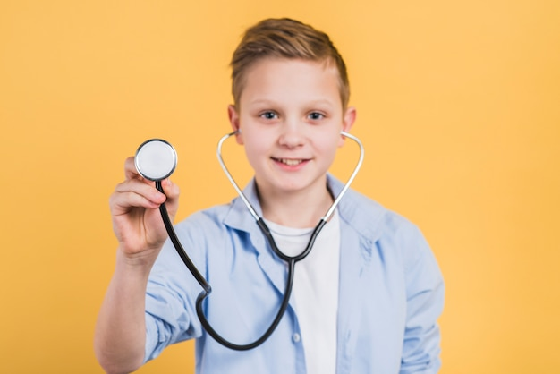 Portret uśmiechnięty chłopiec mienia stetoskop w kierunku kamery pozyci przeciw żółtemu tłu Darmowe Zdjęcia
