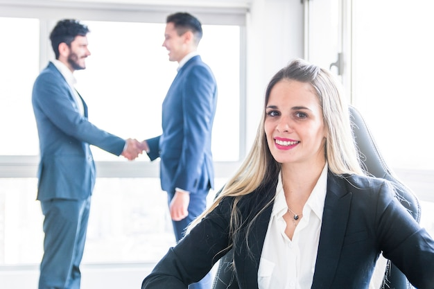 Portret uśmiechnięty młody bizneswoman przed mężczyzna trząść ręki Darmowe Zdjęcia