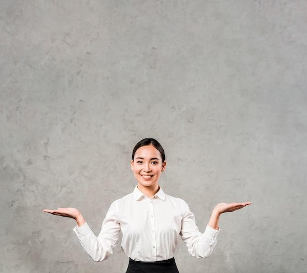 Portret uśmiechnięty młody bizneswoman wzrusza ramionami przeciw szarej betonowej ścianie Darmowe Zdjęcia