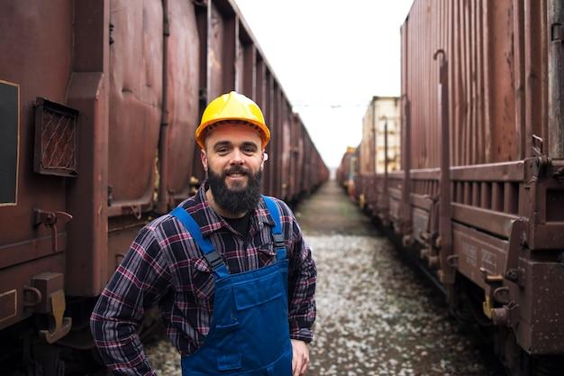 Portret Uśmiechnięty Pracownik Kolei Stojący Między Pociągami Towarowymi Darmowe Zdjęcia
