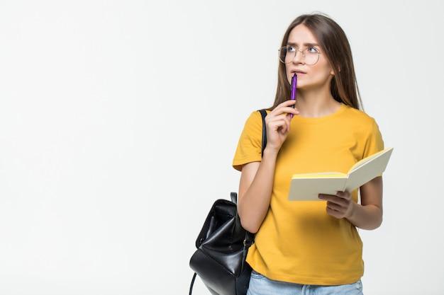 Portret Uśmiechnięty Przypadkowy Dziewczyna Uczeń Z Plecaka Writing W Notepad Podczas Gdy Stojący Z Książkami Odizolowywać Nad Biel ścianą Darmowe Zdjęcia