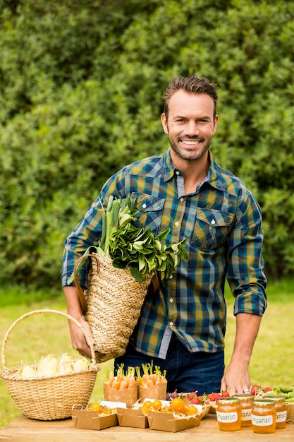 Portret uśmiechnięty przystojny mężczyzna sprzedaje organicznie warzywa Premium Zdjęcia