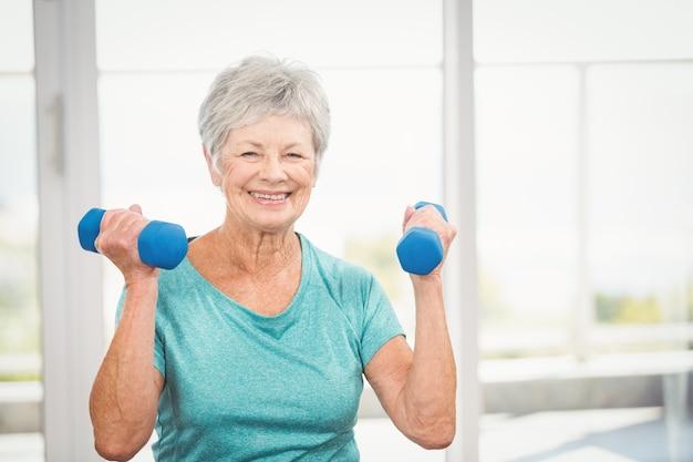 Portret uśmiechnięty starszy kobiety mienia dumbbell Premium Zdjęcia