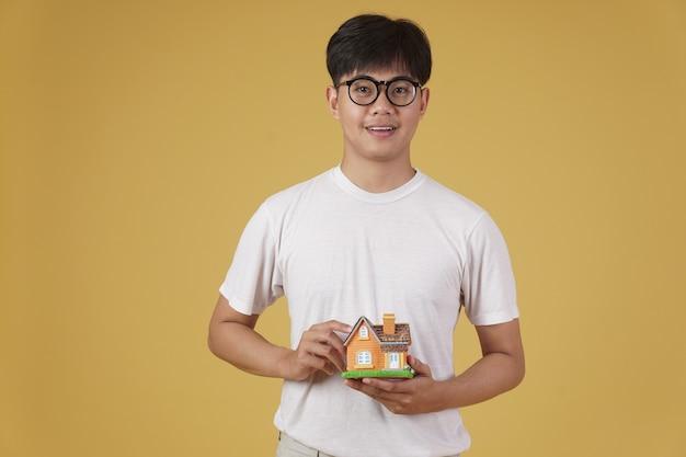 Portret Uśmiechnięty Szczęśliwy Wesoły Młody Azjatycki Mężczyzna Ubrany Niedbale Z Modelu Domu Na Białym Tle. Koncepcja Zakupu Nieruchomości Premium Zdjęcia