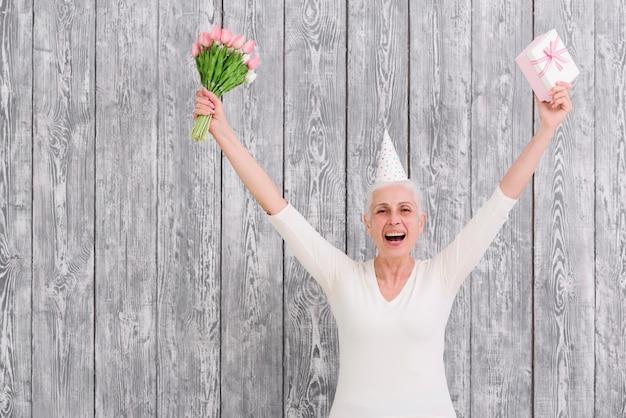 Portret Uśmiechnięty Urodzinowy Kobiety Mienia Kwiatu Bukiet Z Prezenta Pudełkiem Przed Drewnianym Tłem Darmowe Zdjęcia