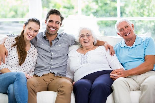 Portret uśmiechnięty wielopokoleniowy rodzinny obsiadanie na kanapie Premium Zdjęcia