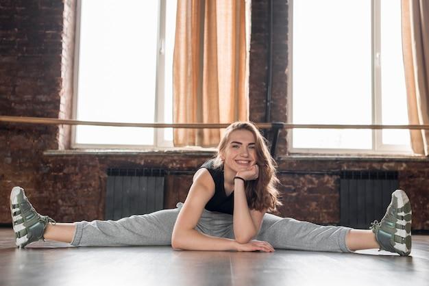 Portret uśmiechnięty żeński tancerz siedzi na podłoga z jego rozpostartymi nogami Darmowe Zdjęcia