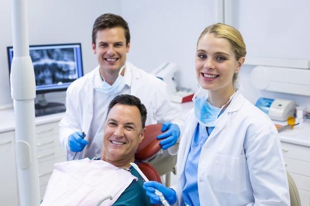 Portret Uśmiechniętych Dentystów I Pacjenta Płci Męskiej Premium Zdjęcia