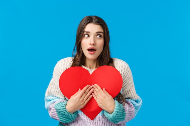 Portret W Pasie Zaskoczony I Ciekawy, Zastanawiająca Się Kaukaska Kobieta Nie Wie, Kto Przygotował Dla Niej Prezent Na Walentynki, Rozglądając Się Zdziwiony, Otwierając Słodkie Czerwone Kartonowe Serce Premium Zdjęcia