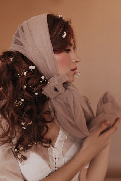 Portret W Profilu Kręcone Kobiety Z Kwiatami W Ciemnych Włosach Pozowanie Na Beżowym Tle. Darmowe Zdjęcia