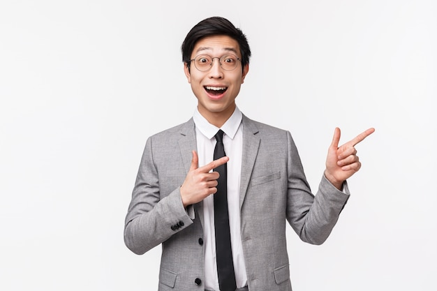 Portret W Talii Podekscytowany I Zaskoczony, Szczęśliwy Azjatycki Biznesmen W Szarym Garniturze, Pokazujący Coś Niesamowitego, świetną Reklamę, Baner Promocyjny Po Prawej Stronie Miejsca Na Kopię Na Białej ścianie Premium Zdjęcia