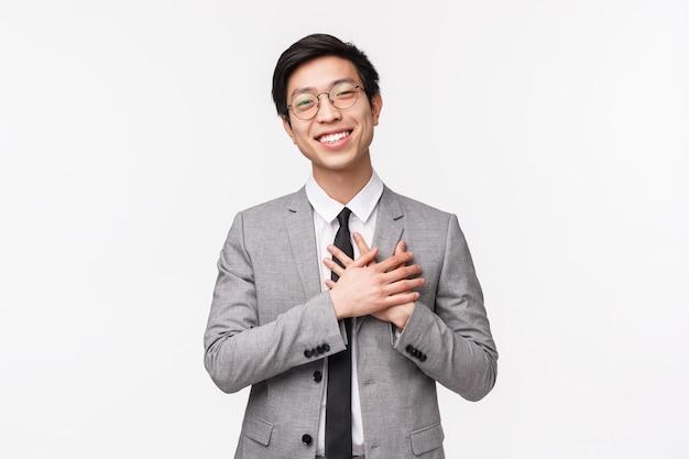 Portret W Talii Wdzięcznego, Pochlebnego Azjatyckiego Młodego Kierownika Biura, Przedsiębiorcy Trzymającego Się Za Serce I Uśmiechającego Się, Dziękującego Za Komplement, Pochlebnego I Wdzięcznego Za Pochwały, Na Białej ścianie Premium Zdjęcia