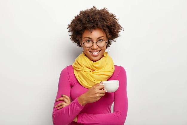 Portret Wesołej Afroamerykanki Z Radosnym Wyrazem Twarzy, Nosi Okulary Optyczne, Trzyma Kubek Napoju, Nosi Okulary Optyczne, Różowy Golf I Szalik, Odizolowane Na Białym Tle Darmowe Zdjęcia