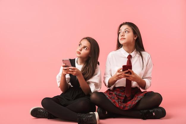Portret Wesoły Dziewczyny W Mundurku Szkolnym Za Pomocą Telefonów Komórkowych, Siedząc Na Podłodze Na Białym Tle Nad Czerwoną ścianą Premium Zdjęcia