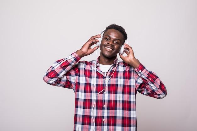 Portret Wesoły Młody Człowiek Afro Amerykański, Słuchanie Muzyki W Słuchawkach I śpiew Na Białym Tle Darmowe Zdjęcia