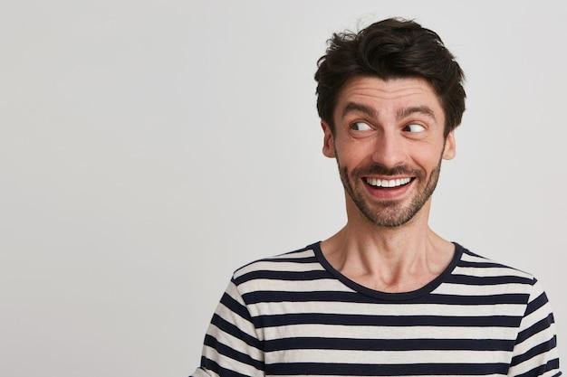 Portret Wesoły Przystojny Brodaty Młody Człowiek Nosi Koszulkę W Paski, Uśmiechając Się I Patrzy Z Boku Na Białym Tle Darmowe Zdjęcia