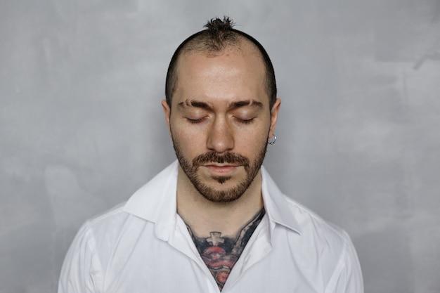 Portret Wytatuowany Brodaty Mężczyzna W Białej Koszuli Z Zamkniętymi Oczami Darmowe Zdjęcia