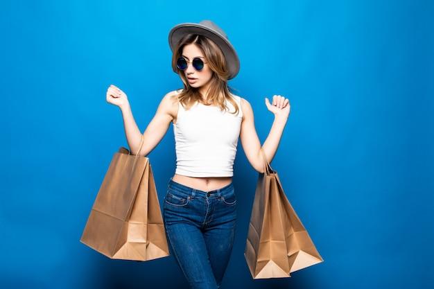 Portret Z Podnieceniem Piękna Dziewczyna Jest Ubranym Suknię I Okulary Przeciwsłonecznych Trzyma Torba Na Zakupy Odizolowywających Nad Błękit ścianą Darmowe Zdjęcia