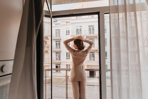 Portret Z Tyłu Zrelaksowana Kobieta W Brązowym Stroju. Zdjęcie Zadowolony Stylowej Pani Pozuje W Pobliżu Dużego Okna. Darmowe Zdjęcia