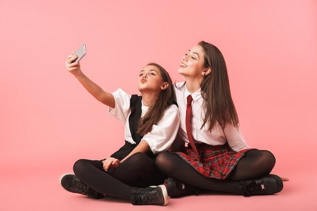 Portret Zabawnych Dziewcząt W Mundurkach Szkolnych Przy Użyciu Telefonów Komórkowych Do Zdjęć Selfie, Siedząc Na Podłodze Odizolowanej Na Czerwonej ścianie Premium Zdjęcia