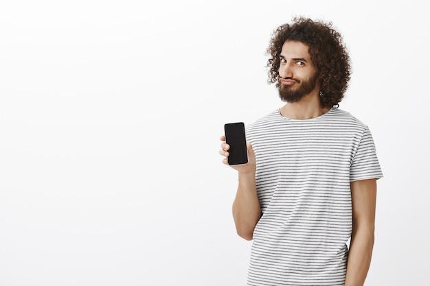 Portret Zadowolony Figlarny Brodaty Mężczyzna Ze Wschodu Z Fryzurą Afro, Pokazując Smartfon Darmowe Zdjęcia