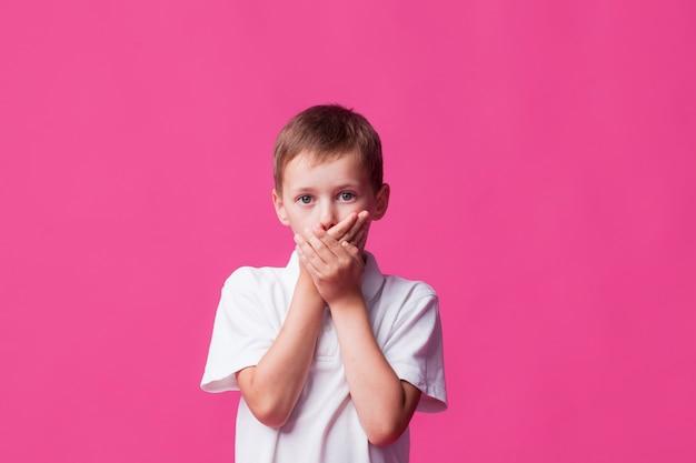 Portret zakrywa jego usta na różowym tle chłopiec Darmowe Zdjęcia