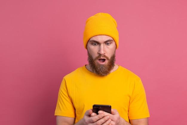 Portret Zaniepokojonego, Zszokowanego Dojrzałego Brodatego Mężczyzny, Sapiącego Nieszczęśliwie, Trzymającego Smartfona, Czytającego Dziwną I Niepokojącą Wiadomość Na Różowo Darmowe Zdjęcia
