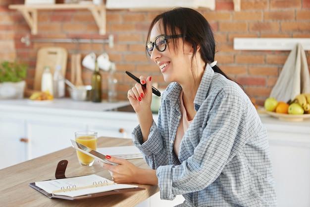 Portret Zapracowanej Kobiety Tworzy Projekt, Wyszukuje Informacje W Tablecie, Pisze Notatki W Notesie Darmowe Zdjęcia