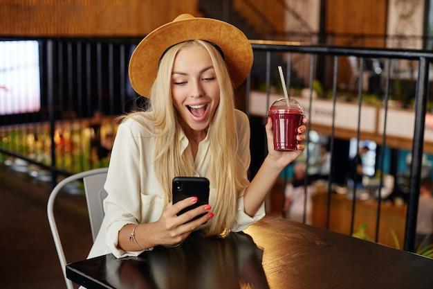 Portret Zaskoczonej, Dość Długowłosej Blondynki W Szerokim Brązowym Kapeluszu I Białej Koszuli Siedzącej W Restauracji Podczas Przerwy Obiadowej, Pijącej Smoothie I Sprawdzającej Portale Społecznościowe Na Swoim Telefonie Komórkowym Darmowe Zdjęcia