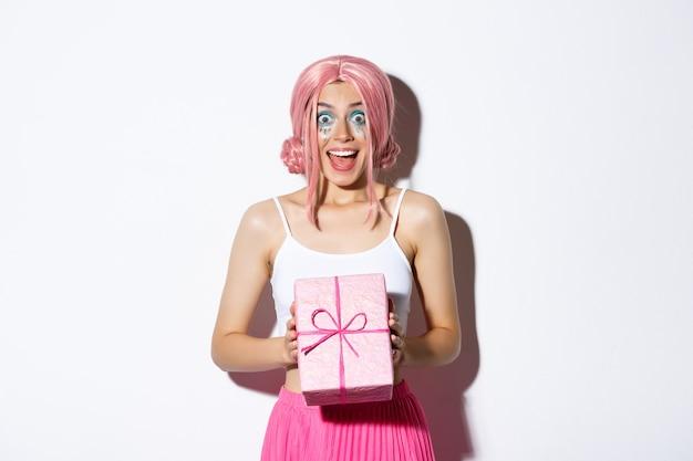 Portret Zaskoczony, Atrakcyjna Dziewczyna Wyglądająca Podekscytowana, Odbiera Prezent Na Urodziny, Ubrana W Różową Perukę, Stojąca. Darmowe Zdjęcia
