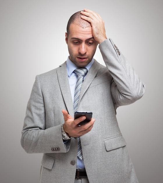Portret zaskoczony człowiek patrząc na jego smartphone Premium Zdjęcia