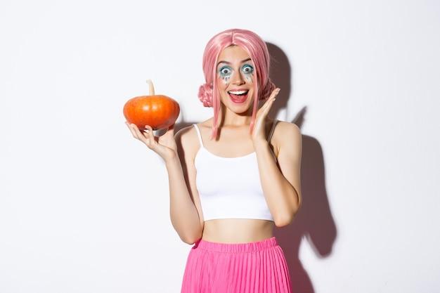 Portret Zaskoczony Dziewczyna W Różowej Peruce, Trzymając Dyni I Patrząc Podekscytowany, świętuje Halloween, Stojąc. Darmowe Zdjęcia