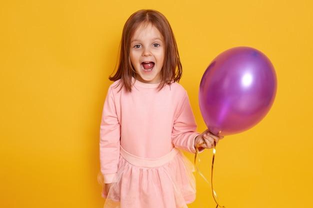 Portret Zaskoczony Dziewczynka Z Ciemnymi Prostymi Włosami Stojący Na żółtym Studio Piękne Ubrania, Trzymając Fioletowy Balon W Ręce Darmowe Zdjęcia