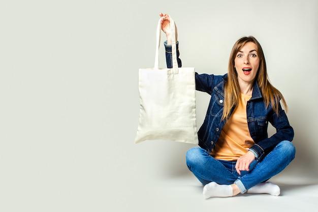 Portret Zaskoczony Młoda Kobieta Siedzi Ze Skrzyżowanymi Nogami, Trzymając Lnianą Torbę Z Zakupami Na Jasnym Tle Premium Zdjęcia