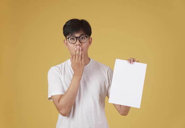 Portret Zaskoczony Młody Człowiek Azjatycki Ubrany Niedbale Pokazuje Pusty Papier Pusty Afisz Na Białym Tle. Premium Zdjęcia