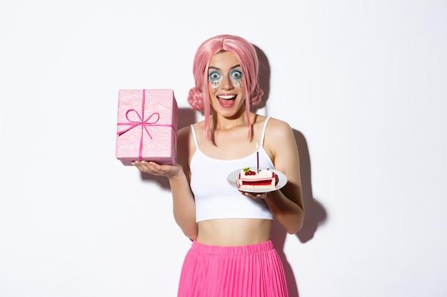 Portret Zaskoczony Piękna Dziewczyna W Różowej Peruce, Odbiera Prezent Urodzinowy, Trzymając Tort Urodzinowy I Uśmiechnięty Szczęśliwy, Stojący. Darmowe Zdjęcia