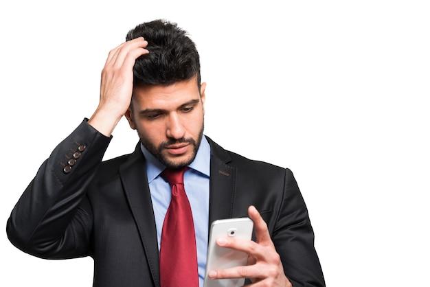 Portret zmartwiony mężczyzna patrzeje jego smartphone Premium Zdjęcia