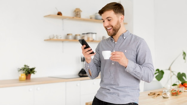 Portreta Mężczyzna Pije Kawę Podczas Gdy Sprawdzać Wiszącą Ozdobę Darmowe Zdjęcia