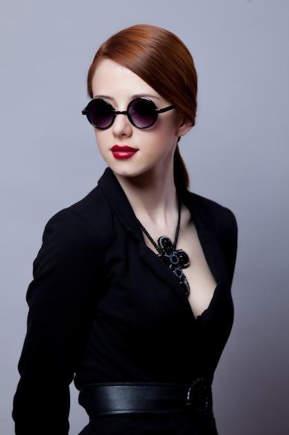 Portriat Stylu Rudowłosej Dziewczyny W Czarnych Ubraniach Na Szaro Premium Zdjęcia