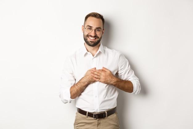 Poruszony I Wdzięczny Biznesmen Trzymający Się Za Ręce Na Sercu, Uśmiechnięty Wdzięczny, Stojący Darmowe Zdjęcia