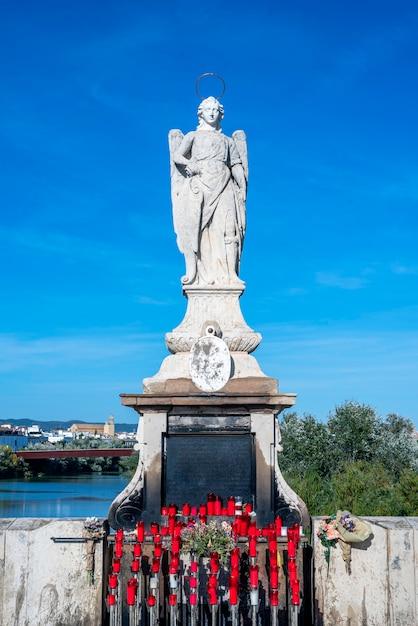 Posąg świętego Ze świecami I Kwiatami U Jego Stóp, A Za Nim Błękitne Niebo I Rzeka Premium Zdjęcia