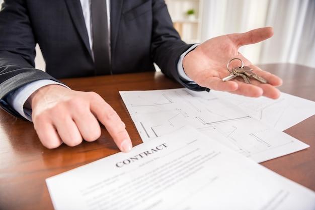 Pośrednik pokazuje kontakt z kluczem z nowego mieszkania. Premium Zdjęcia