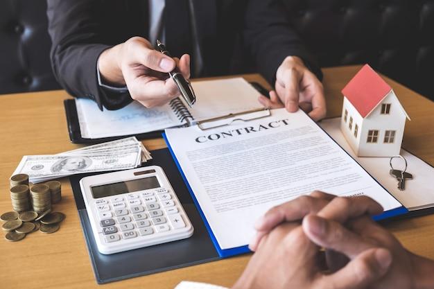 Pośrednik w obrocie nieruchomościami daje długopis klientowi podpisującemu umowę o nieruchomości z zatwierdzoną formą hipoteki Premium Zdjęcia