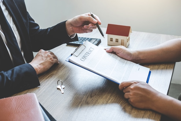 Pośrednik w obrocie nieruchomościami osiąga formularz umowy do podpisania przez klienta umowy o nieruchomości z zatwierdzonym Premium Zdjęcia