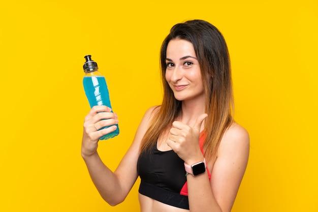 Potomstwa bawją się kobiety nad odosobnioną ścianą z butelką soda Premium Zdjęcia