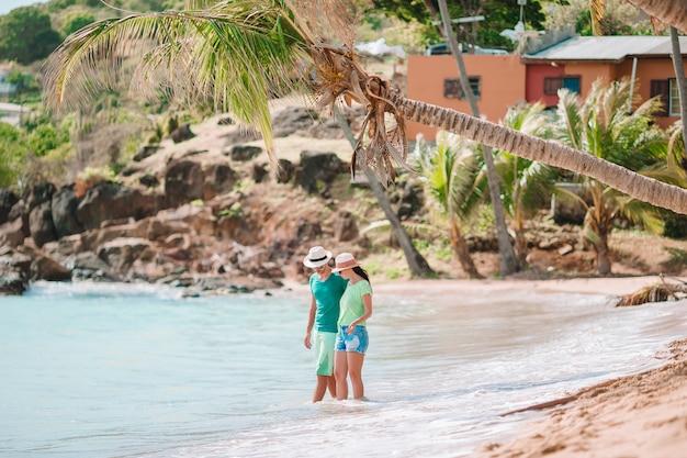 Potomstwa dobierają się odprowadzenie na tropikalnej plaży z białym piaskiem i turkusową ocean wodą przy antigua wyspą na karaiby Premium Zdjęcia