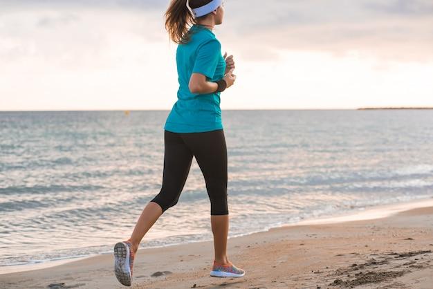 Potomstwa Dostosowywali Dziewczyna Bieg Na Plaży Przy Wschodem Słońca W Ranku Premium Zdjęcia