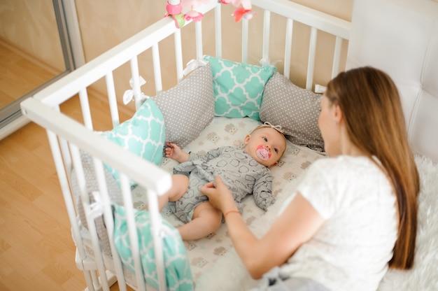Potomstwa Matkują Kołysać ślicznej Małej Nowonarodzonej Dziewczynki W łóżku Premium Zdjęcia