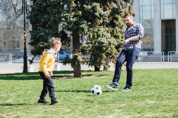 Potomstwa Ojcują I Jego Syn Bawić Się Piłkę Nożną W Parku Darmowe Zdjęcia
